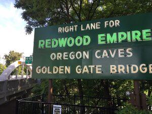 Signs at Caveman Bridge in Grants Pass pointing to Redwood Empire & Golden Gate Bridge
