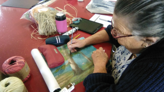 """Karen Runcell restores a damaged painting for the """"358"""" Exhibition."""