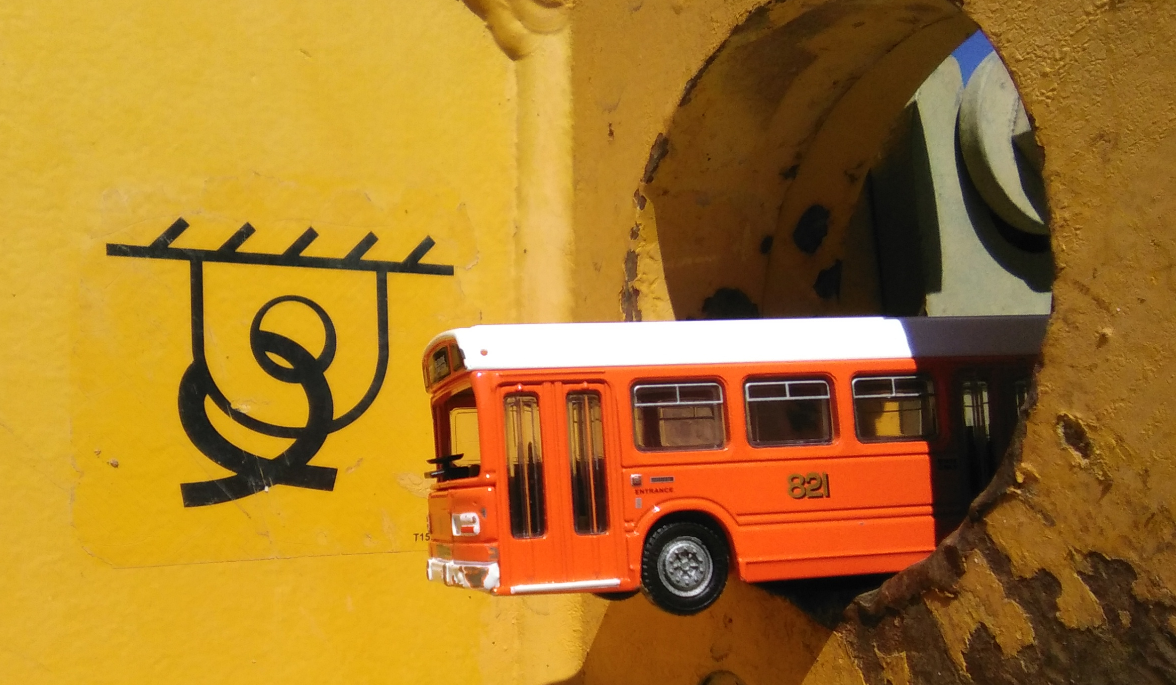 An orange toy passenger bus sticks through a metallic hole in a yellow background of a road building machine, with an interesting symbol printed in black.