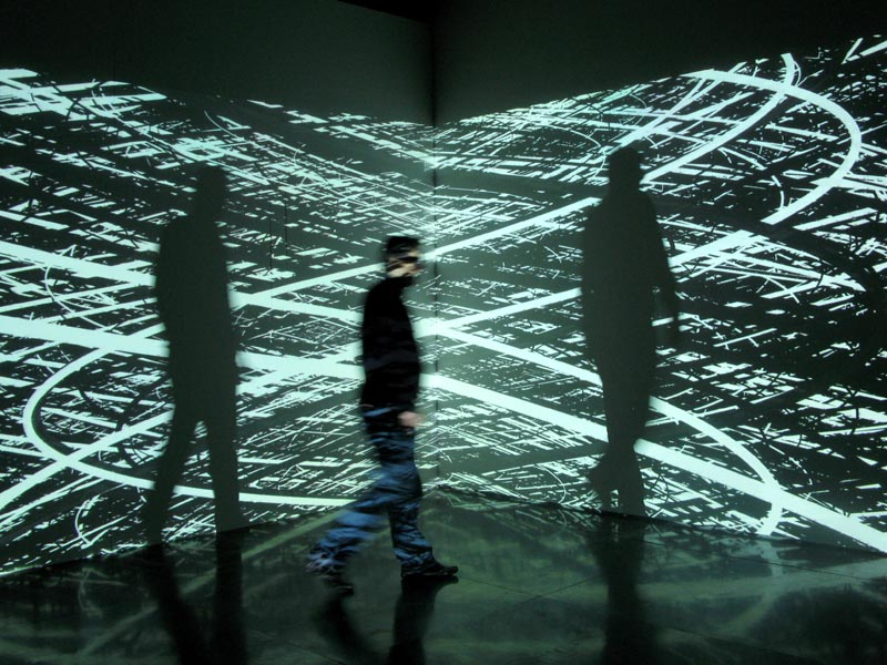 A moving human figure stands in front of and between screens with patterned light projections on them.