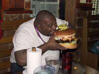 Ciccione che addenta un hamburger.jpg
